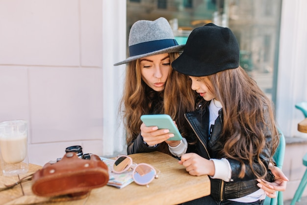 Interested young woman in felt hat looking at blue smartphone which holding little girl in leather jacket.