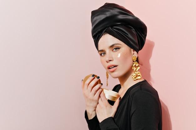 Заинтересованная молодая женщина в ювелирных изделиях делает свой уход за кожей