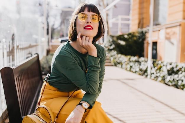 通りに座っている黄色いズボンに興味のある若い女性。ベンチでポーズをとっている魅力的なブルネットの女の子の屋外写真。