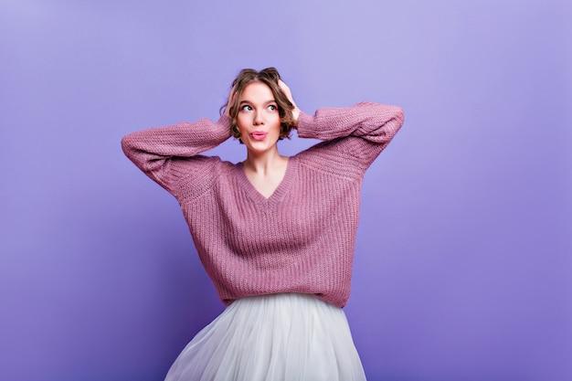 Giovane donna interessata in maglione oversize che tocca la sua testa sul muro viola. sognante ragazza dai capelli corti in gonna bianca che gode del servizio fotografico.