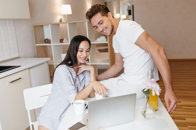 Interested young woman pointing at laptop screen with smile, spending time with boyfriend in morning