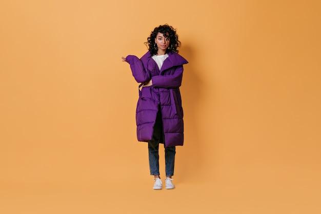 紫色のダウンジャケットでポーズをとる興味のある若い女性