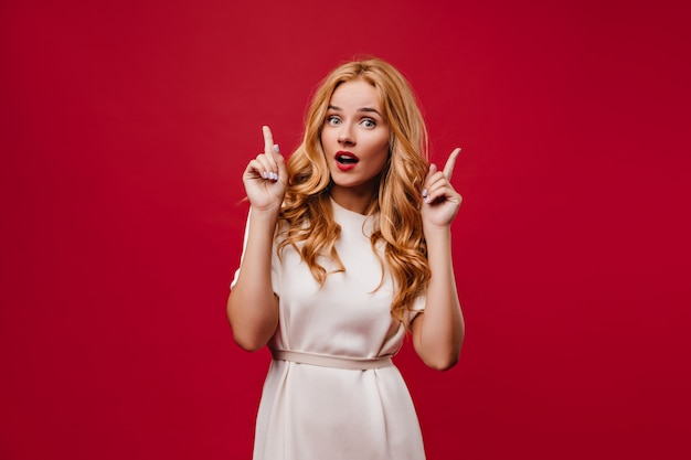 Interested young woman with long wavy hair posing with mouth open. debonair stylish girl in white dress standing on red wall.
