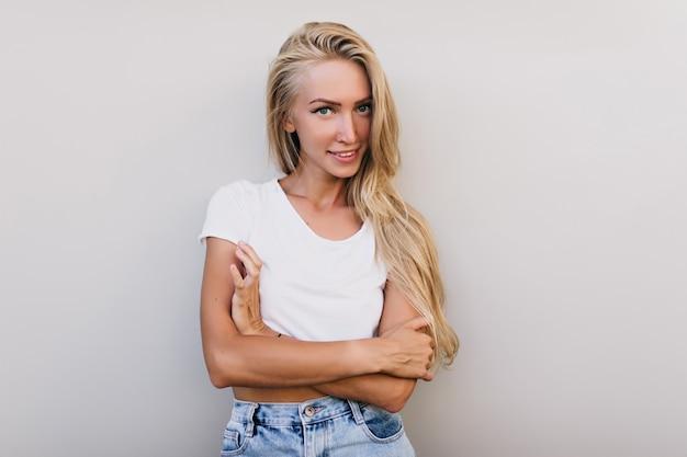 スタジオでポーズをとる日焼けした肌を持つ興味のある若い女性。夏のタンクトップで喜んでいる白人女性の屋内ショット。