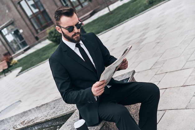 Interesting article. good looking young man in full suit reading a newspaper while sitting outdoors