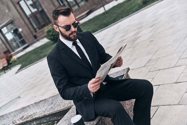 興味深い記事。屋外に座って新聞を読んでフルスーツの格好良い若い男