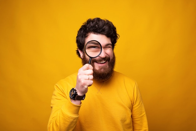 Interesting bearded man is looking through a magnifying glass at the camera.