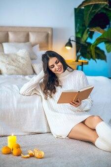 Интересную книгу. молодая красивая женщина читает книгу и смотрит