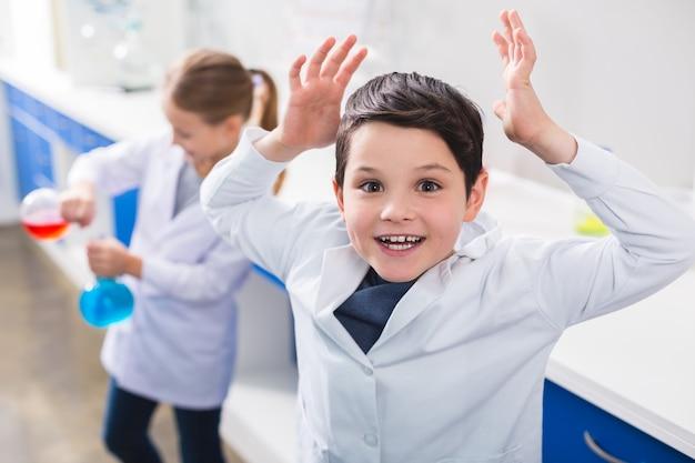 興味深い化学。化学実験をしながら手を上げてあなたを見ている幸せな素敵な賢い男の子