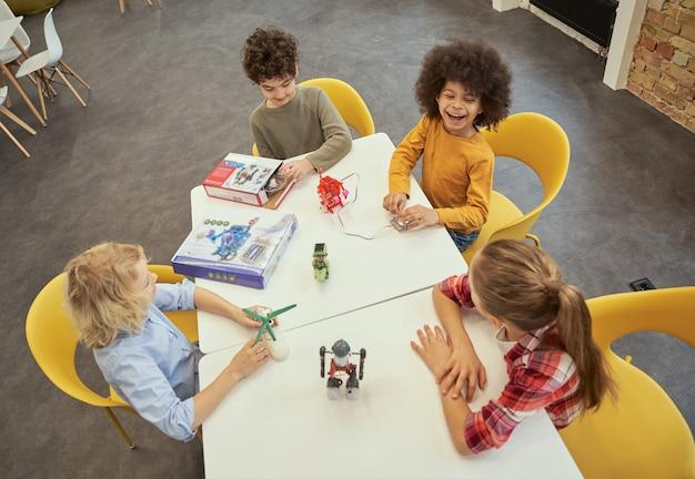 기술을 검사하는 테이블에 앉아 있는 행복한 다양한 아이들의 흥미로운 수업 높은 각도 보기