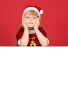 Интересное copyspace. вертикальный снимок маленькой девочки, смотрящей вниз на пустой плакат с copyspace
