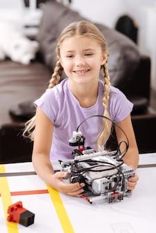 面白いサイバーおもちゃ。ロボット工学研究室に座って、積極性を表現しながらサイバーロボットを保持している笑顔の陽気な面白がって女の子