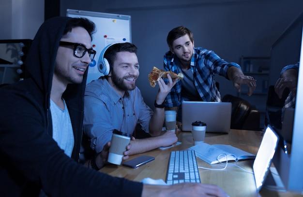 Интересное развлечение. позитивные красивые симпатичные программисты сидят в офисе и смотрят на экран ноутбука, весело вместе
