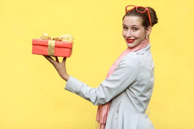 노란색 배경에 선물 상자를 들고 프로필을 서 있는 흥미로운 생강 젊은 성인 여성