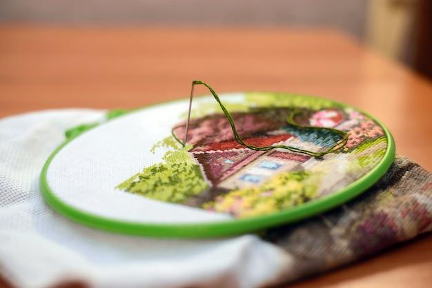 針と緑の糸で仕事をしている自宅からの興味深い手刺繡