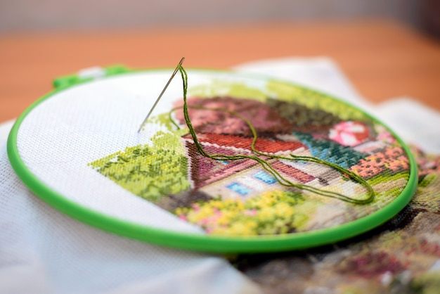 Interesting hand embroidery from home in work with a needle and green thread