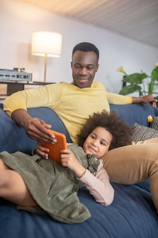 Interesting here. dark-skinned young smiling dad with little cute daughter looking at tablet at home on comfortable sofa
