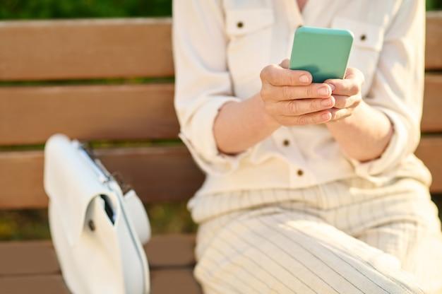 흥미롭네요. 스마트폰이 야외 벤치에 앉아 있고 얼굴이 없는 가벼운 정장을 입은 여성의 깔끔한 아름다운 손