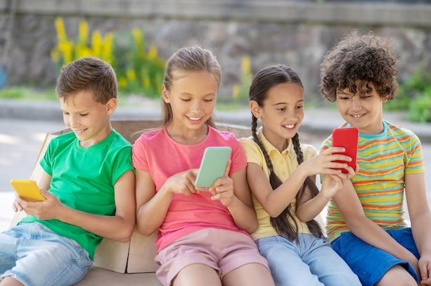 흥미롭네요. 화창한 날 야외에 앉아 스마트폰을 바라보며 웃고 있는 관심 있는 소년 소녀들