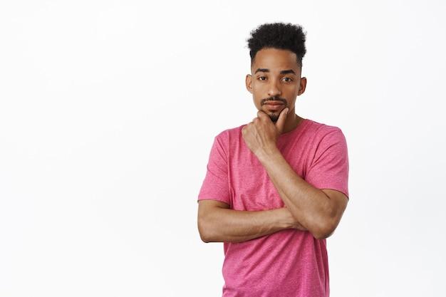 Интересно, хм. задумчивый афро-американский мужчина думает, трогает подбородок, обдумывает решение, рассматривает что-л., стоя в розовой футболке на белом.