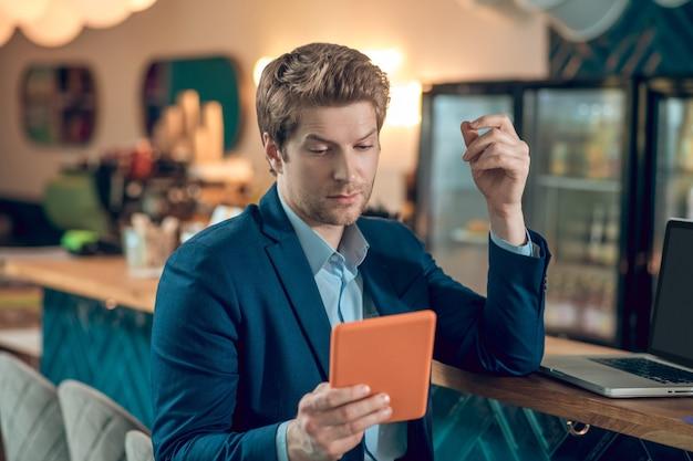 흥미로운 정보. 카페 바에서 노트북 근처에 앉아 태블릿에 관심을 보이는 파란색 정장을 입은 젊은 성인 남성