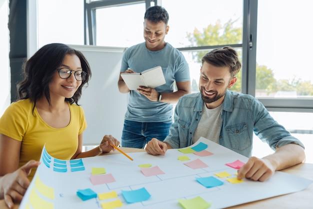흥미로운 직업. 밝고 긍정적 인 창의적인 사람들이 함께 앉아 작업을 즐기면서 즐거운 시간을 보냅니다.