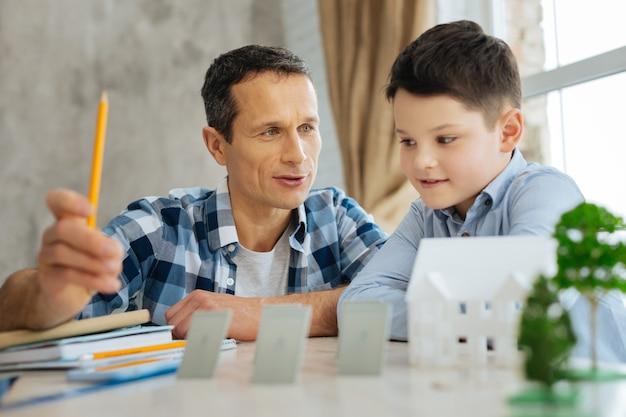 흥미로운 교훈. 10 대 이전의 아들에게 대체 에너지 원에 대해 이야기하는 매력적인 청년, 탁자 위에 태양 전지판 미니어처로 수업을 예시합니다.