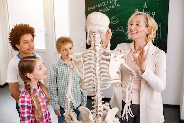 興味深いレッスン。人間の骨について話している間、骨格を指している喜んでいる賢い先生