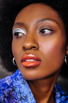 Interesting look. dark-skinned model with big earrings looking serious while posing for the photo