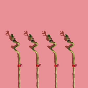 복숭아 배경에 대나무 막대기의 흥미로운 패턴입니다. 최소한의 레이아웃 구성.