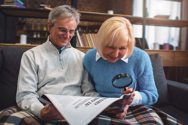 Interesting picture of white-haired man and woman sitting on the sofa