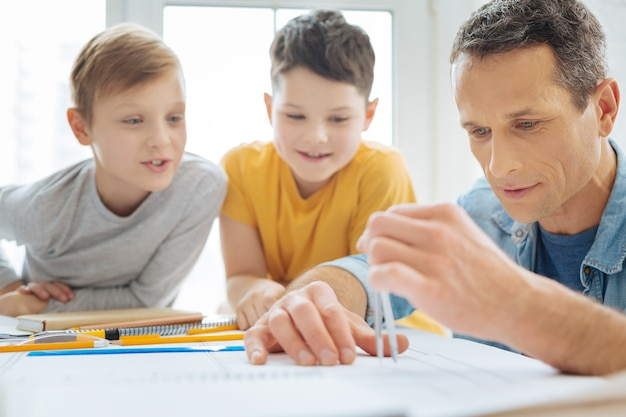 興味深いプロセス。父親のオフィスのテーブルに座って彼が青写真を作成し、コンパスの助けを借りて距離を測定するのを見て大喜びのプレティーンの男の子