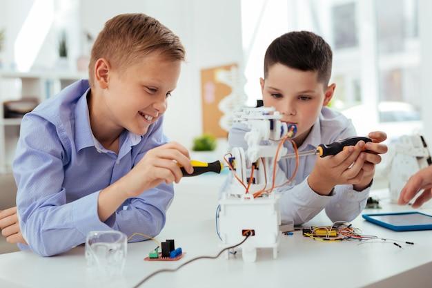 Интересная наука. радостные счастливые мальчики веселятся, собирая робота вместе