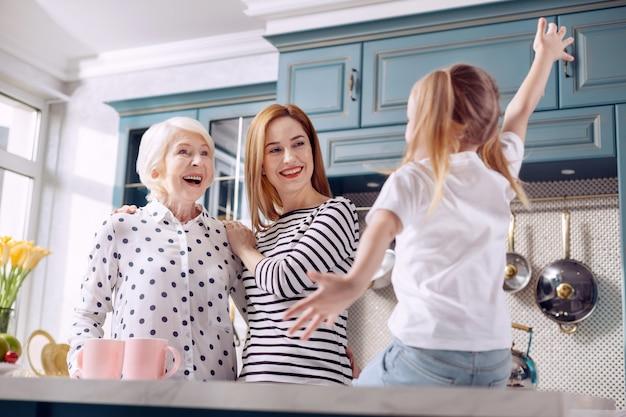 Интересная история. очаровательная маленькая девочка сидит на кухонном столе и делится захватывающей историей со своими любимыми мамой и бабушкой, много жестикулируя