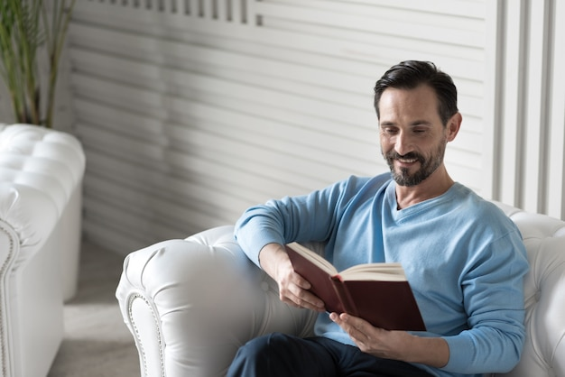 Интересная история. приятный красивый счастливый мужчина держит книгу и читает ее, сидя на диване