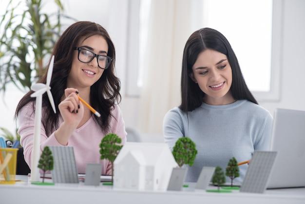 面白い考え。見下ろしながらモデルを作成するポジティブな女性の同僚