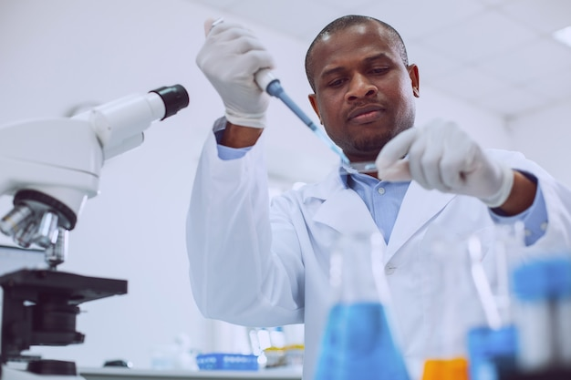 Interesting work. concentrated skilled researcher wearing a uniform and carrying out a test