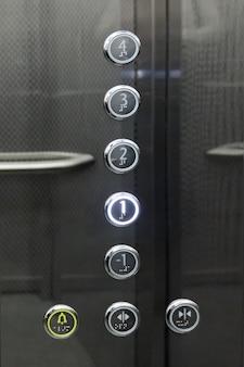 엘리베이터의 금속 버튼의 내부 및 근접 촬영입니다.