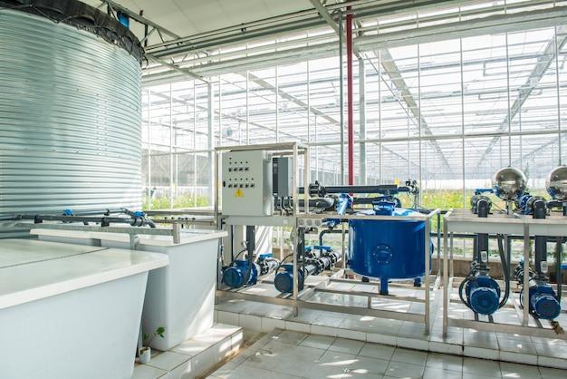 Интерьер и оборудование с трубопроводами и резервуаром для воды в современной теплице