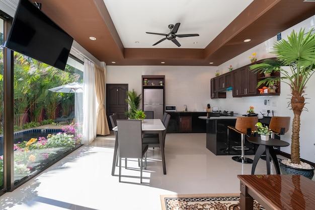 Дизайн интерьера и экстерьера гостиной и обеденной зоны открытого типа с деревянным обеденным столом.