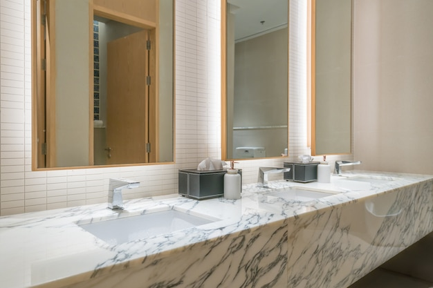 Interior of bathroom with washbasin faucet and black towel in hotel.