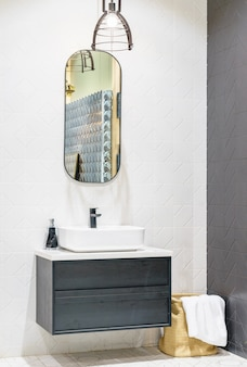 Interior of bathroom with washbasin faucet and white towel.