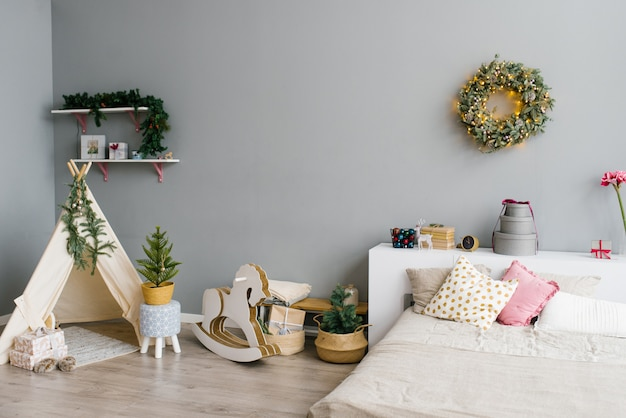 The interior of the bedroom or children's room decorated for christmas or new year: bed, wigwam, children's swing horse, christmas wreath on the wall