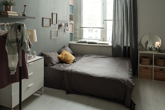 Interior of bedroom with bed furniture rack for clothes and other stuff