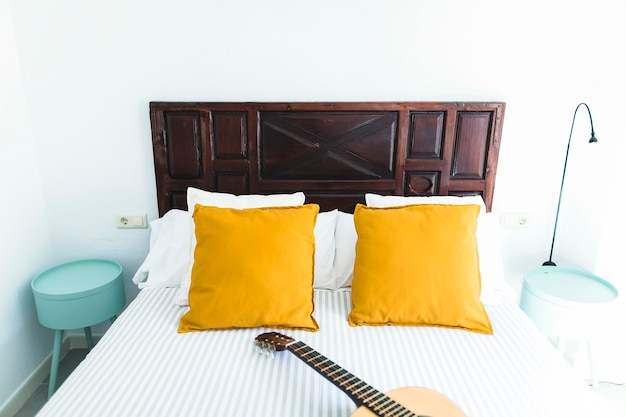 Interior of bedroom with guitar on bed