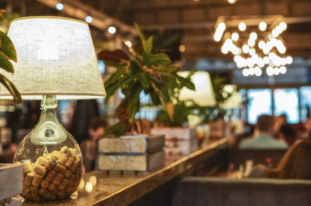 The interior of the cafeteria with a table lamp in a glass bottle filled with wine corks