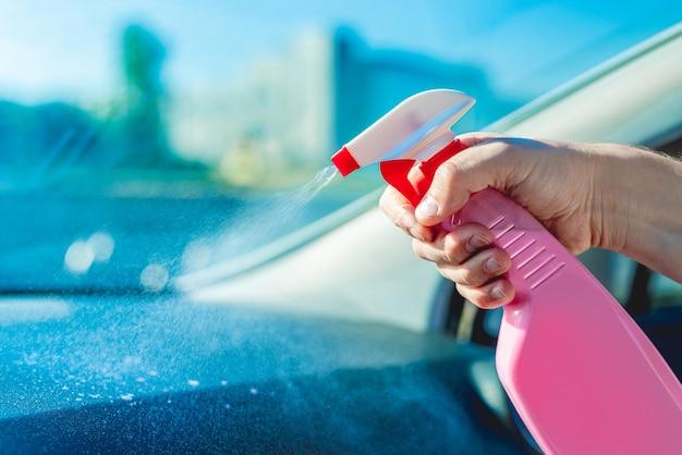 ボトルからスプレーされたクレンザーで車内を洗う