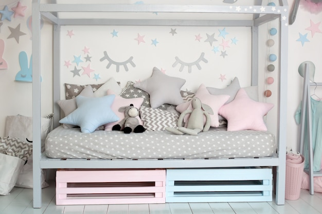 Interior of a children room with a wooden bed in shape of house. home decor. a cozy scandinavian style children bedroom with crafts,toys and cute pillows. bedding and textiles for children nursery.