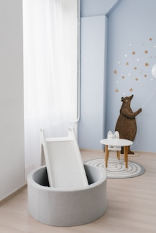 The interior of the children's room is decorated in blue and beige colors. the bear holds a small balloon in his hands. slide with a pool made of plastic balls