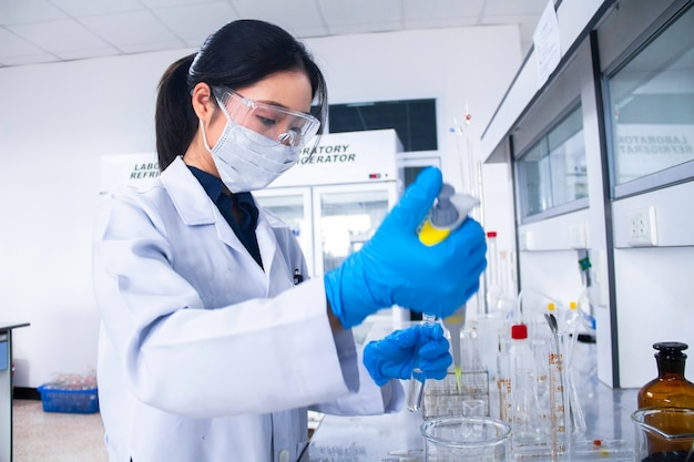 Interior of clean modern white medical or chemistry laboratory. scientist working at a lab with micro pipette and test tubes. laboratory concept with asian woman chemist. selective focus.